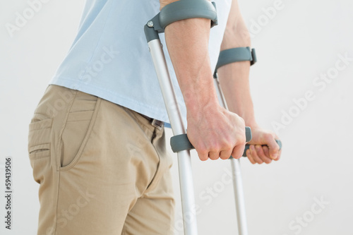 Close-up mid section of a man with crutches Fototapeta