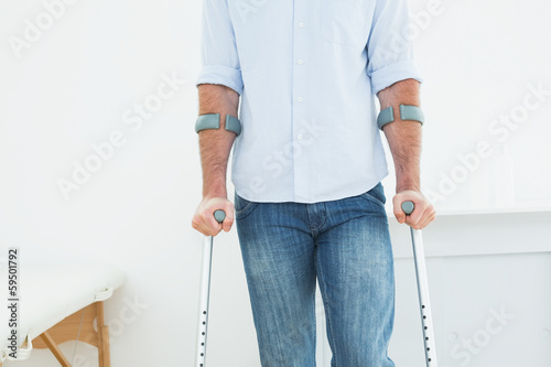 Obraz na płótnie Mid section of a man with crutches in medical office