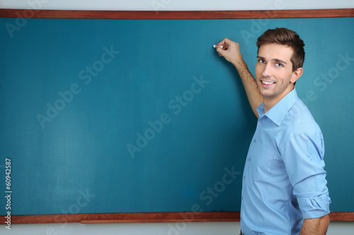 Photo Young teacher near chalkboard in school classroom