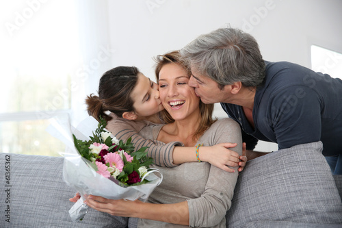 Family celebrating mother's day with bunch of flowers