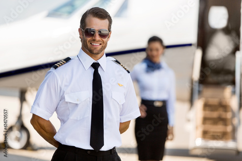 Slika na platnu Pilot Standing With Stewardess And Private Jet At Terminal