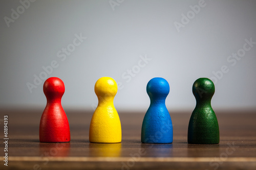 Fotografiet Four pawn figurines, team concept, table, grey background