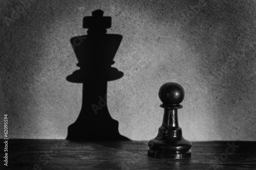 Fotografiet Chess pawn standing in a spotlight that make a shadow  actistic