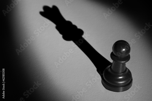 Chess pawn standing in a spotlight that make a shadow of queen a Fototapet