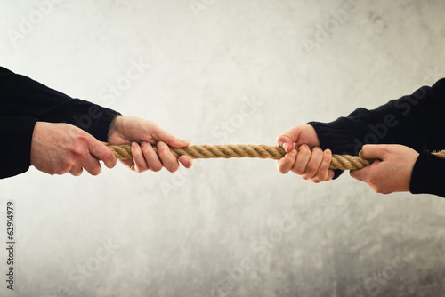 Photo Tug of war. Hands pulling rope to opposite sides