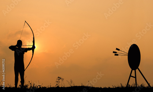 Foto Silhouette archery shoots a bow at the target.