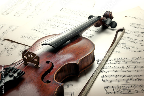 Canvas Print Old scratched violin with sheet music. Vintage style.