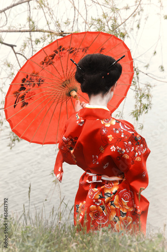 Geisha with red umbrella at the riverside (back view)