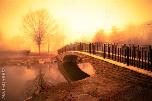 Canvastavla morning light and fog over pond with footbridge