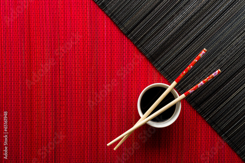 Chopsticks and bowl with soy sauce on bamboo mat