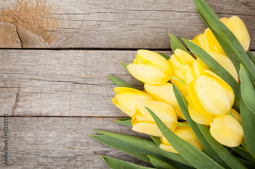 Fresh yellow tulips over wooden table #65323535