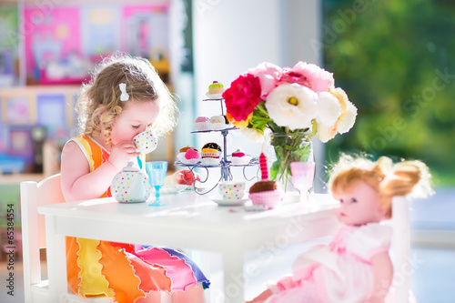 Fotografia Toddler girl playing tea party with a doll