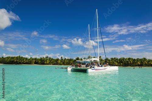 White catamaran on azure water against blue sky Fotobehang