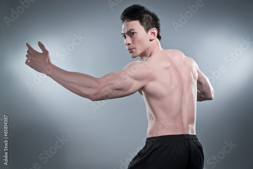 Fotografia Muscled asian kung fu man in action pose. Wearing black pants. S