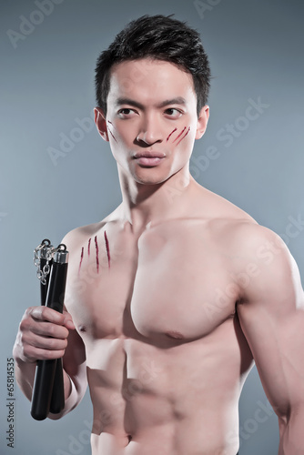 Obraz na płótnie Muscled asian kung fu man with nunchucks. Blood scratches on his