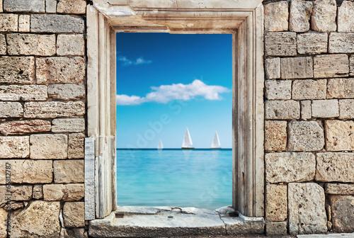 Fototapeta Widok z okna w ścianie z kamieni na morze i żaglówki ścienna