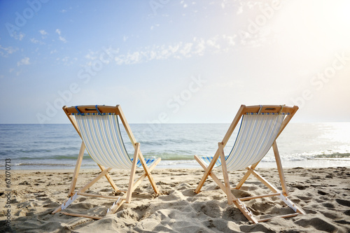 Fotografia couple of chairs on sandy beach at sunset - relaxation concept