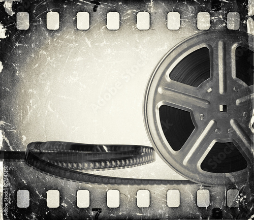 Grunge old motion picture film reel with film strip. #67543150
