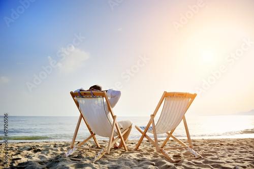 Obraz na płótnie man relaxing on the beach sitting on deck chair