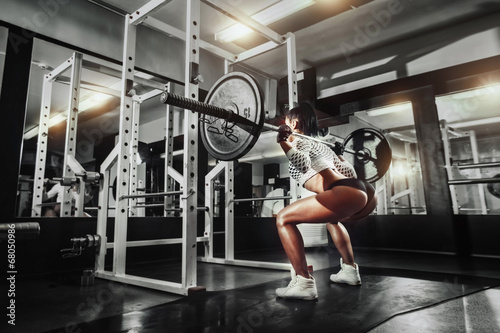 Young sexy girl in the gym doing squat with barbell