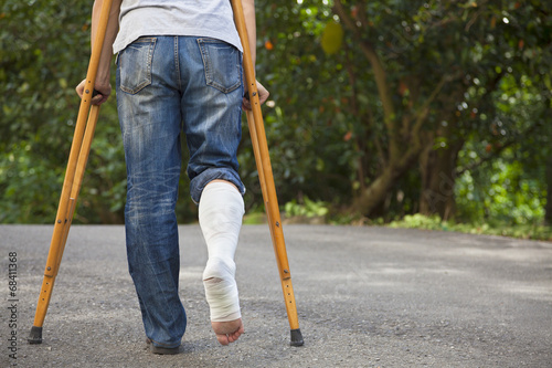 Fotografia Young asian man on crutches with tree background