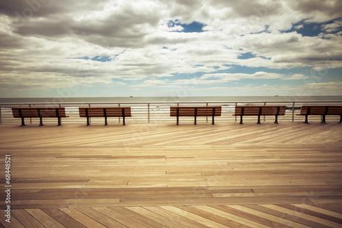 Obraz na płótnie Vintage tone seaside boardwalk with benches