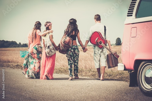 Fototapeta Multi-ethnic hippie friends with guitar and luggage