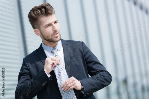 Photo Junger Geschäftsmann bindet Krawatte