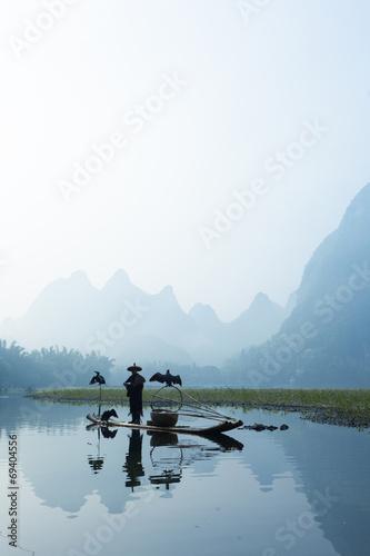 Obraz na płótnie Cormorant, fish man and Li River scenery sight with fog in sprin