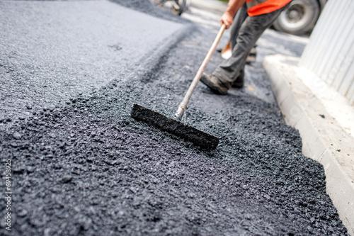 Worker leveling fresh asphalt on a road building Fotobehang