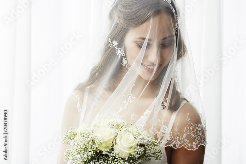 Photo Excited young bride in veil holding bouquet.