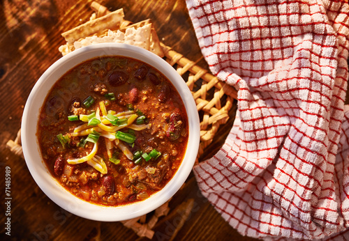 overhead photo of a bowl of chili with cheese and green onions Fototapeta