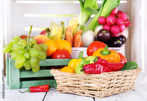 Vegetables in crate and in basket on white wooden box