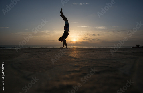 Fotografie, Obraz silhouetted man doing handstand in sunset