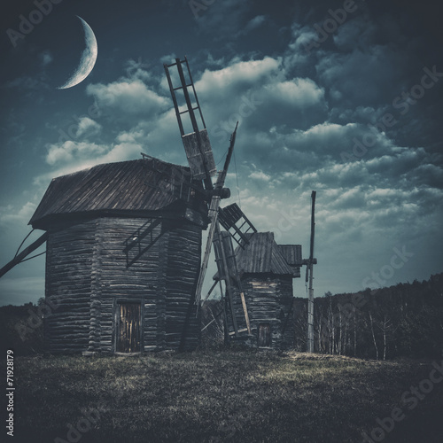 Spooky landscape with few haunted wind mills against dark forest