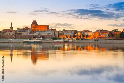 Torun old town reflected in Vistula river at sunset, Poland