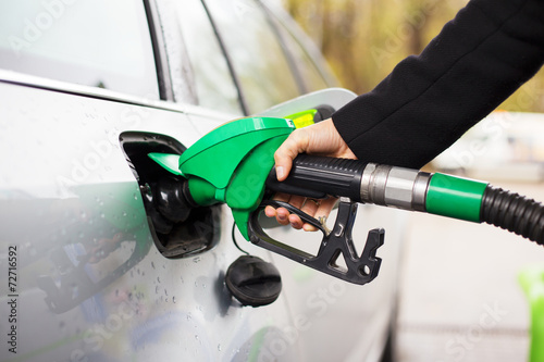 Fotografie, Tablou Hand holding fuel pump and refilling car at petrol station