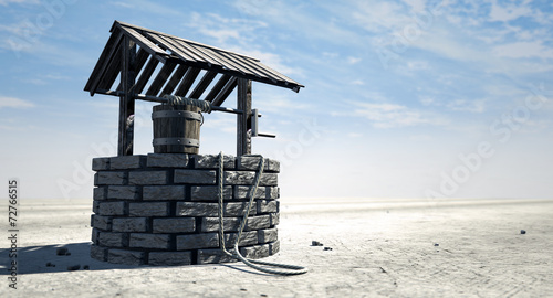 Photo Wishing Well With Wooden Bucket On A Barren Landscape