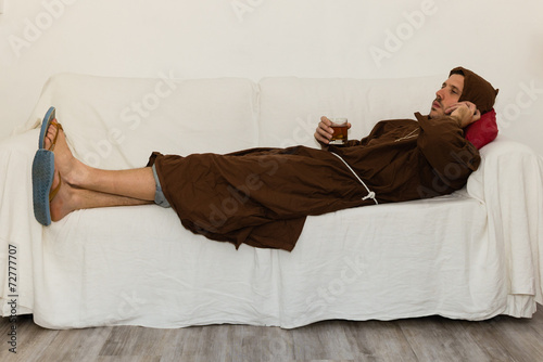 Photo friar drinking and relaxing lying on a white sofa
