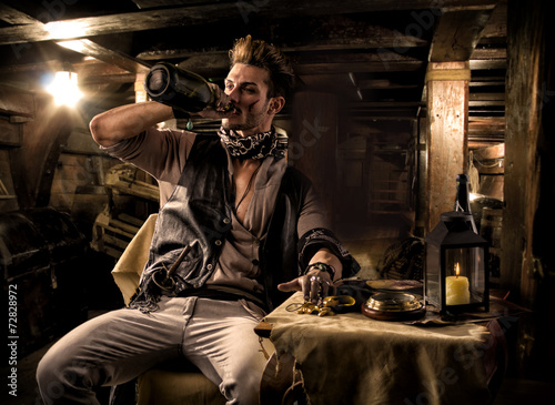 Fotografia Pirate Drinking from Bottle in Ship Quarters