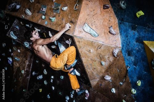 Photo Muscular man practicing rock-climbing on a rock wall indoors