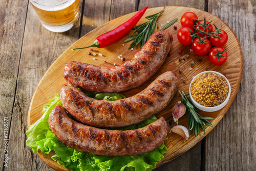 Canvas Print Grilled sausage on a board with vegetables and sauce