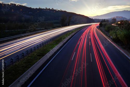 Fotografia Light beams of vehicles on highway.