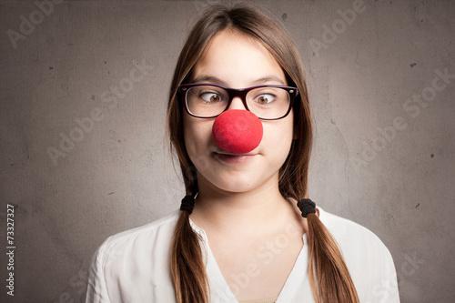 Leinwand Poster Glückliches junges Mädchen mit einer Clownnase