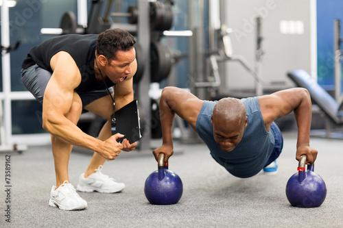 Obraz na plátne personal trainer motivates client doing push-ups
