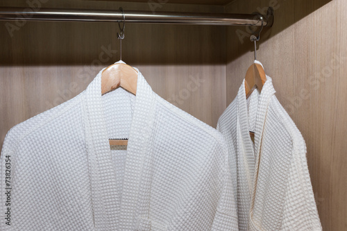Photo white bathrobes hanging in wooden closet