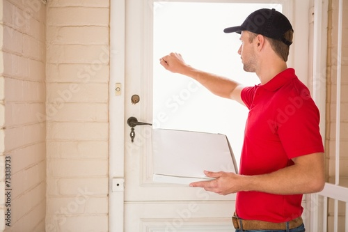 Delivery man holding pizza while knocking on the door Fototapete