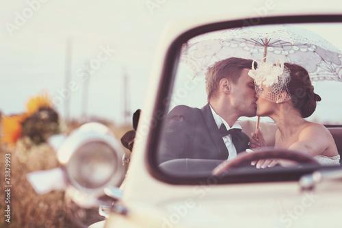 Obraz na plátne Bride and groom in a vintage car