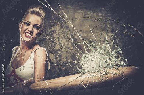 Fototapeta Punk girl breaking glass with a baseball bat