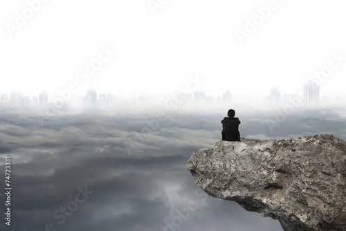 Fotografia man sitting on cliff with gray cloudy sky cityscape background